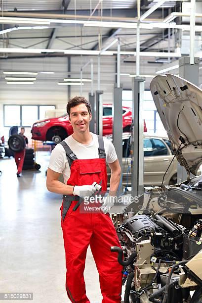 Smiling car mechanic in a workshop