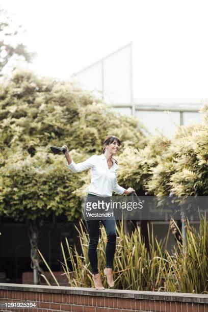 smiling carefree businesswoman holding shoe walking on retaining wall at industry - trabalhadora de colarinho branco imagens e fotografias de stock