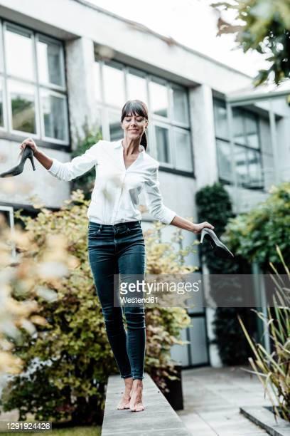 smiling carefree female professional holding shoes while walking on retaining wall at industry - trabalhadora de colarinho branco imagens e fotografias de stock