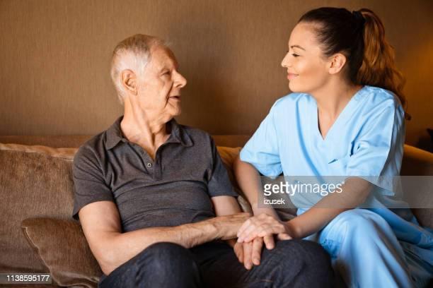 smiling caregiver talking to senior man at home - izusek imagens e fotografias de stock