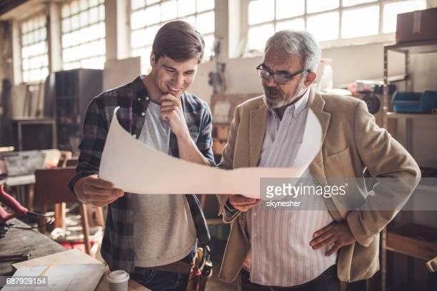 Lächelnd Carpenter und seine Kunden durch Projektpläne in Werkstatt gehen.