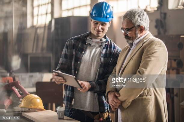 Lächelnd Carpenter und seine Manager mit digital-Tablette in einer Werkstatt.