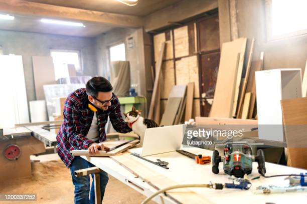 smiling carpenter with cat in workshop - customized stock pictures, royalty-free photos & images