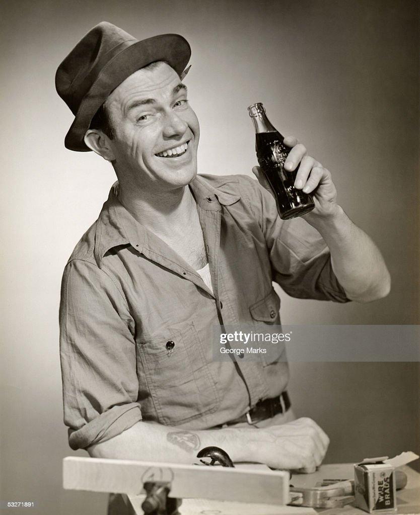 Smiling carpenter with his Coca-Cola : Stock Photo