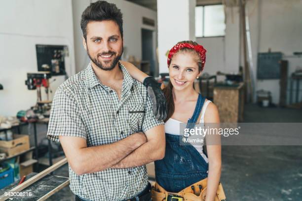 lächelnde tischler in ihrer werkstatt - unterschicht stereotypen stock-fotos und bilder