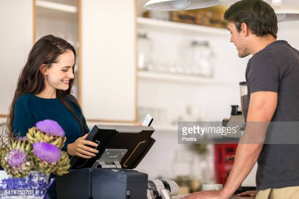 Smiling cashier standing at cash register by man