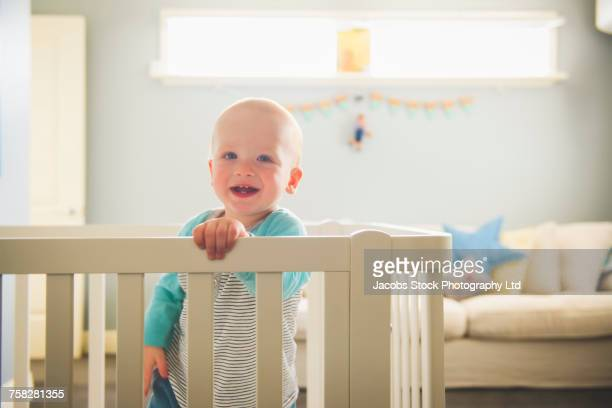Smiling Caucasian baby boy standing in playpen