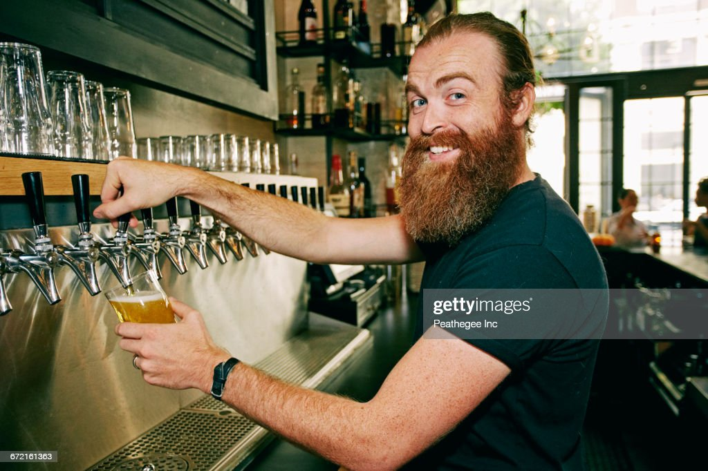 Smiling Caucasian bartender pouring beer : Stock Photo