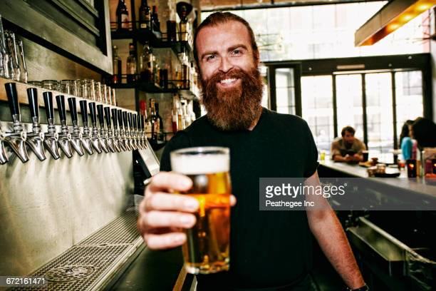 Smiling Caucasian bartender serving beer at bar