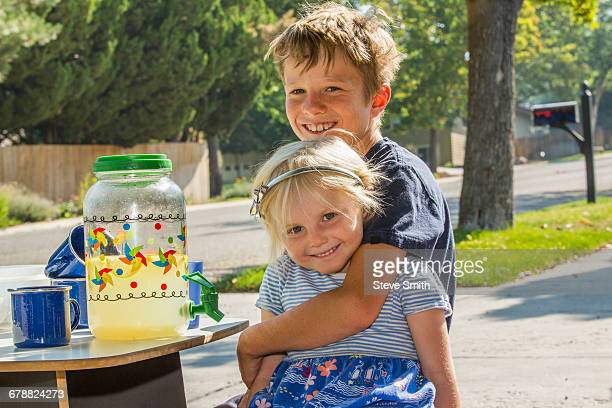 Smiling Caucasian boy hugging girl and selling lemonade