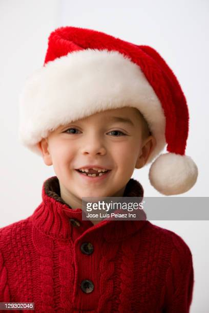 smiling caucasian boy in santa hat - santa hat stock photos and pictures