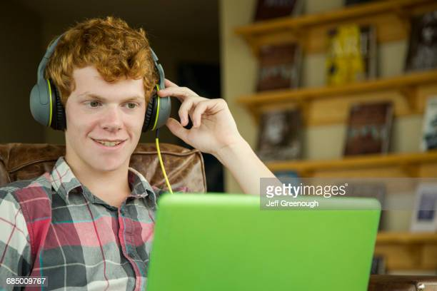 Smiling Caucasian boy listening to laptop with headphones