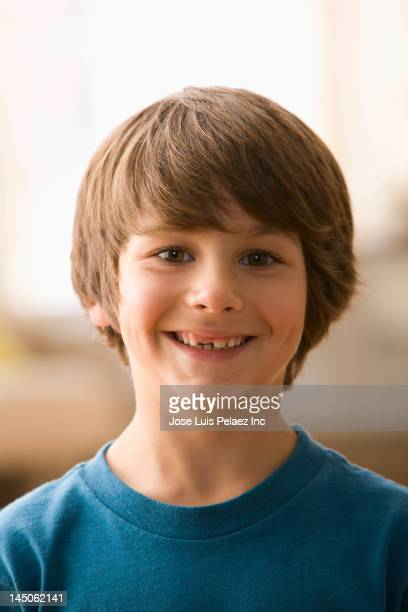 Smiling Caucasian boy with tooth missing