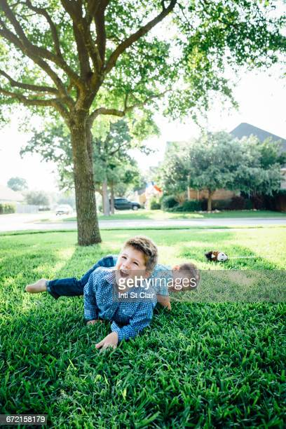 Smiling Caucasian boys playing in grass