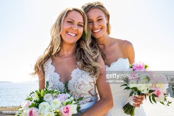 Smiling Caucasian brides holding bouquets