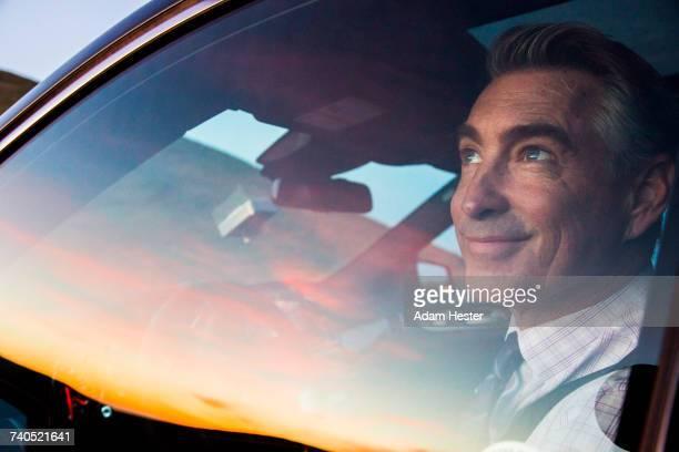 Smiling Caucasian businessman driving car admiring sunset