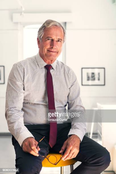 Smiling Caucasian businessman sitting on stool holding eyeglasses