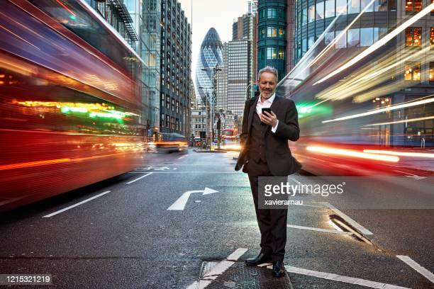 smiling caucasian businessman standing in london street - motion stock pictures, royalty-free photos & images