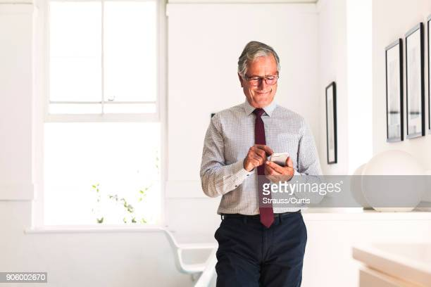 Smiling Caucasian businessman texting on cell phone