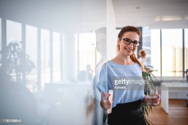 smiling caucasian businesswoman opening office front door - greeting stock pictures, royalty-free photos & images