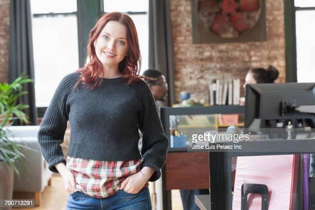 Smiling Caucasian businesswoman posing in office