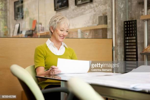 smiling caucasian businesswoman reading paperwork in office - zakelijke kleding stock pictures, royalty-free photos & images