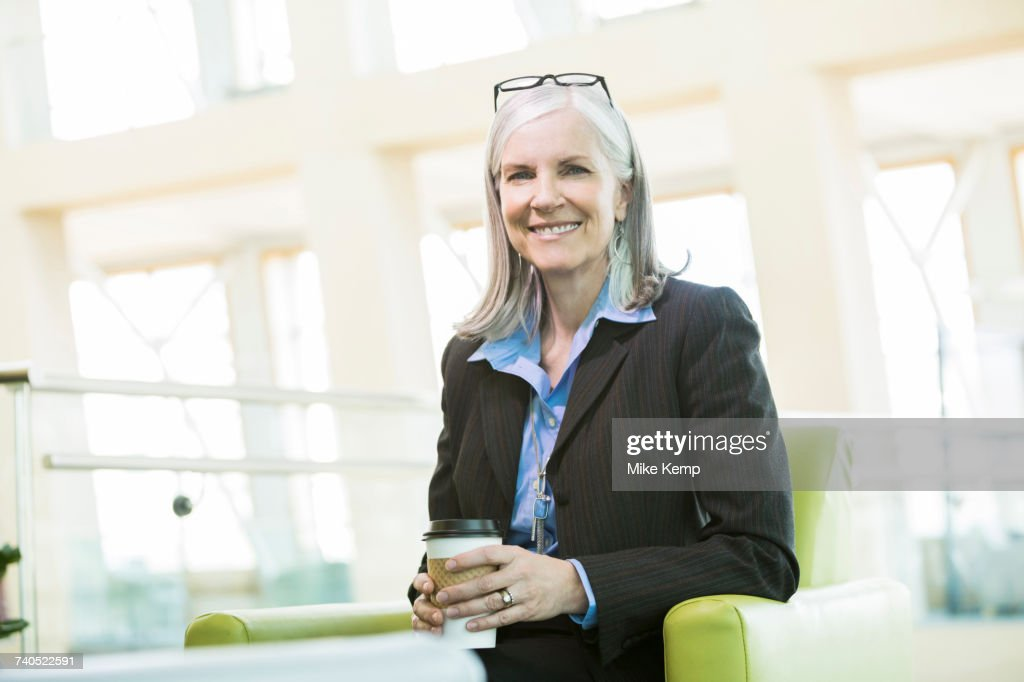 Smiling Caucasian businesswoman sitting in armchair drinking coffee : ストックフォト