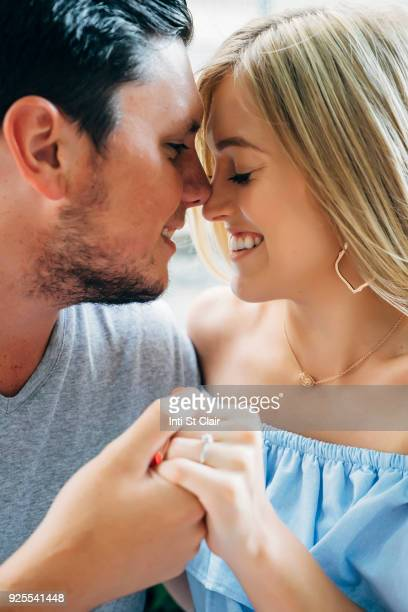 Smiling Caucasian couple holding hands and rubbing noses
