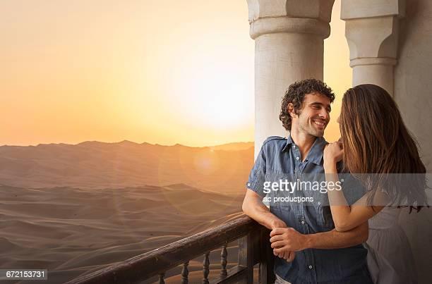 Smiling Caucasian couple on balcony in desert