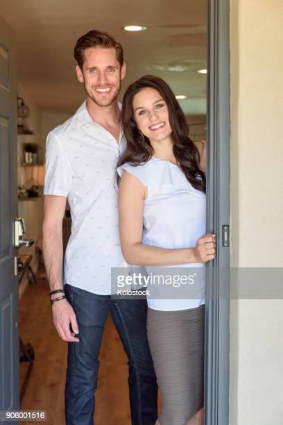Smiling Caucasian couple posing in doorway