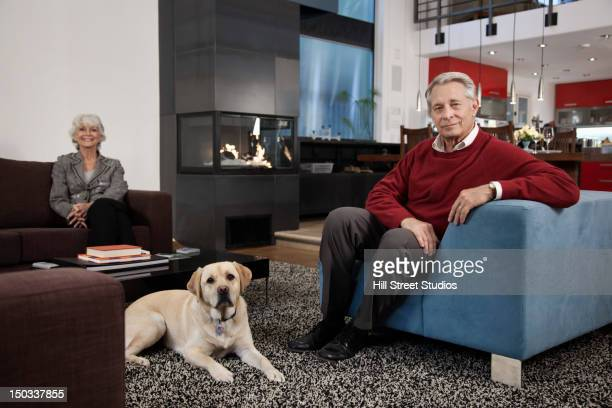 Smiling Caucasian couple sitting together in living room in living room