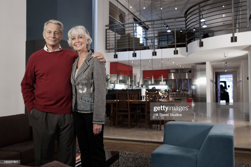Smiling Caucasian couple standing together in living room : Stock Photo