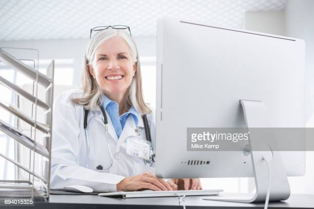 Smiling Caucasian doctor using computer at desk