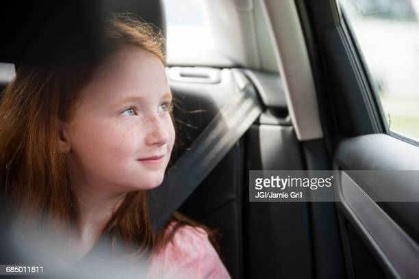 Smiling Caucasian girl in car looking out window