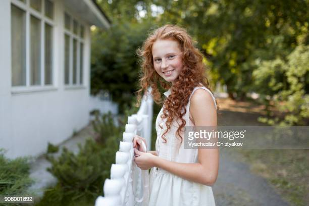 smiling caucasian girl standing near fence - jeune fille rousse photos et images de collection