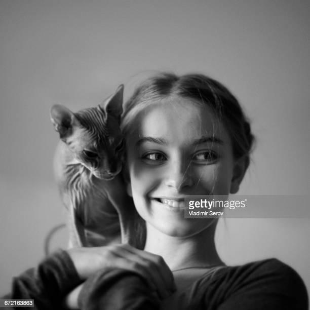 smiling caucasian girl with hairless cat on shoulder - amour noir et blanc photos et images de collection