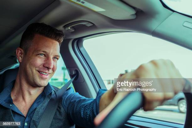 Smiling Caucasian man driving car