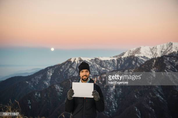 smiling caucasian man holding blank sign in mountain landscape - blank sign stock photos and pictures