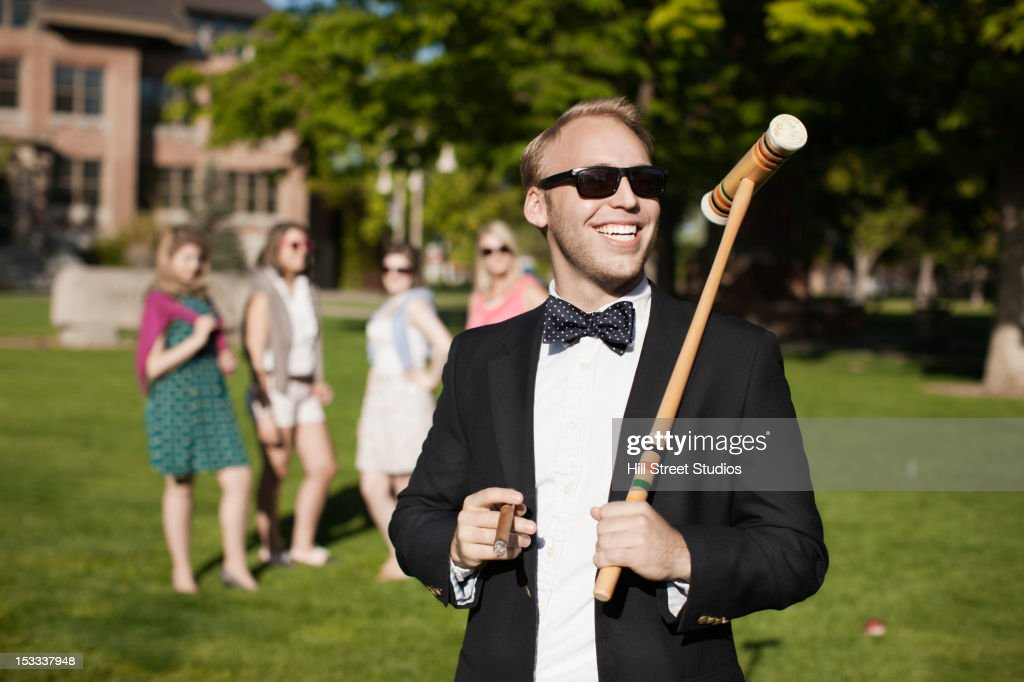 Smiling Caucasian man holding croquet mallet : Stockfoto