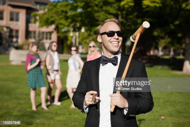 smiling caucasian man holding croquet mallet - high society stock pictures, royalty-free photos & images