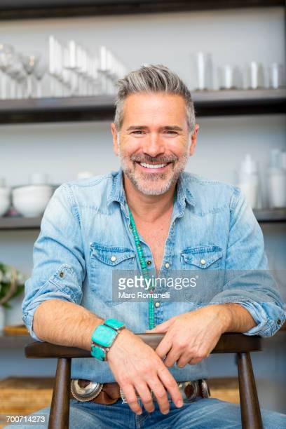 smiling caucasian man leaning on chair in store - alleen oudere mannen stockfoto's en -beelden