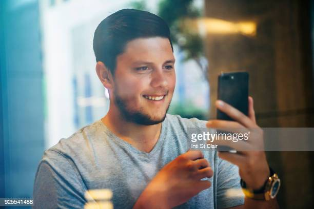 Smiling Caucasian man posing for cell phone selfie