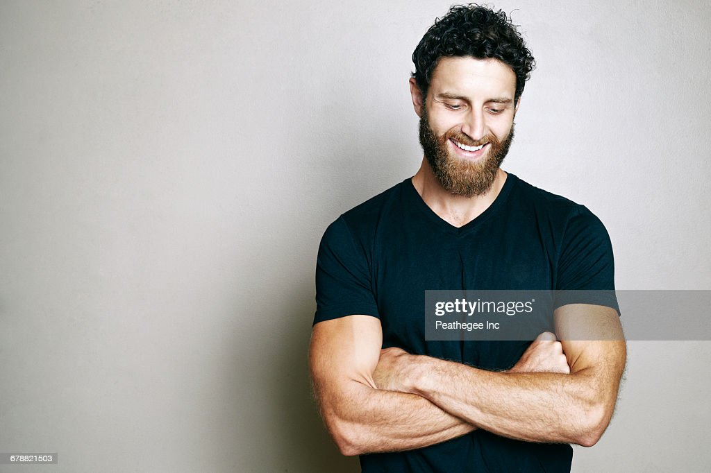 Smiling Caucasian man with beard looking down : Stock Photo