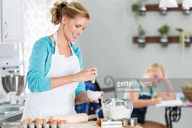 Smiling Caucasian woman cracking open an egg
