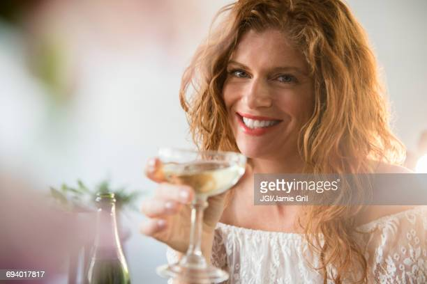 Smiling Caucasian woman drinking champagne in coupe