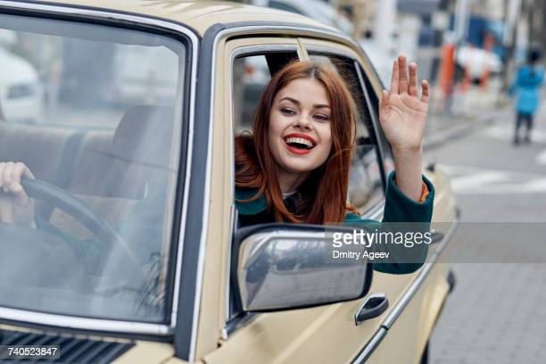smiling caucasian woman driving car and waving - waving gesture stock photos and pictures