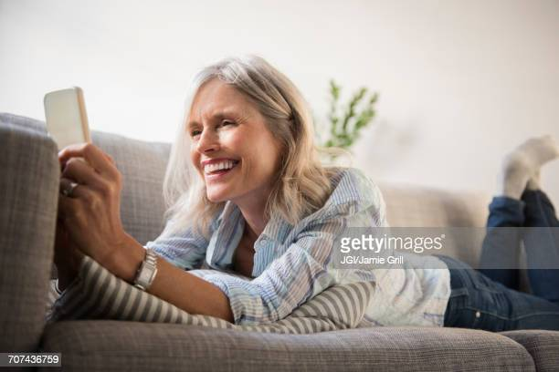Smiling Caucasian woman laying on sofa texting on cell phone