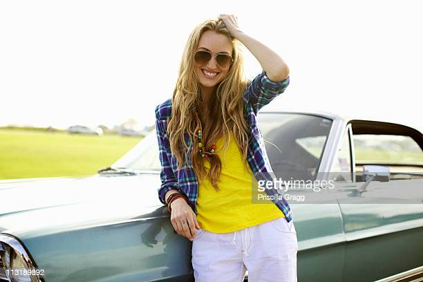 smiling caucasian woman leaning against car - cool cars stock pictures, royalty-free photos & images