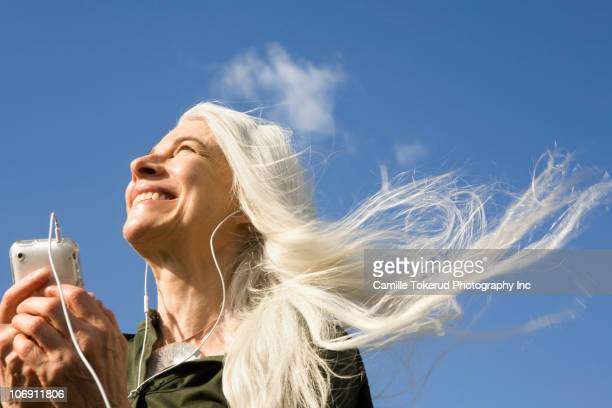 smiling caucasian woman listening to headphones and holding mp3 player - gray hat stock pictures, royalty-free photos & images