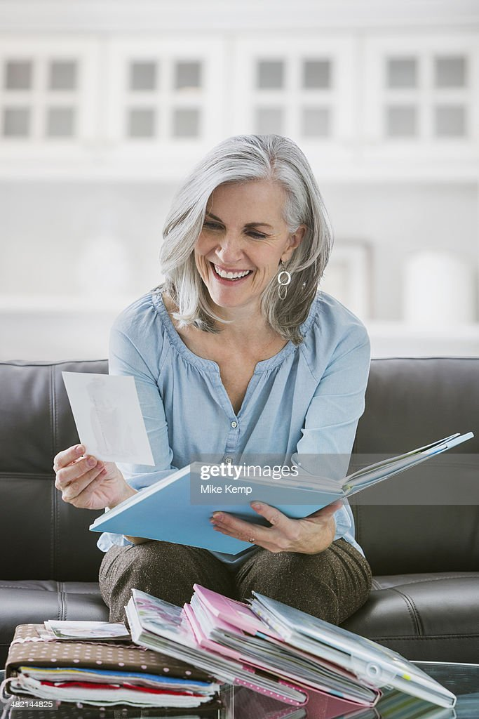 Smiling Caucasian woman looking at photograph albums : Stock Photo